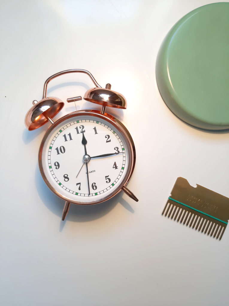 picture of white table from above. An alarm clock lies facing upwards, with the time reading 12:10. The the right is a credit card sized hair comb with the words, 'thrive in the urban jungle.' In the top right corner you can also see the green base of a desk lamp.