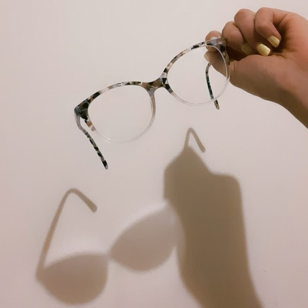 A hand is holding a pair of grey and white tortoise shell glasses. The lighting casts a shadow against a wall behind which is full, giving the illusion of being cast by a pair of sunglasses.